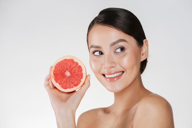 Chiuda in su della donna felice con pelle fresca sana che tiene il pompelmo sugoso e che osserva da parte con il sorriso, isolato sopra bianco Foto Gratuite