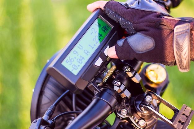 Chiuda in su della mano dell'uomo che fa clic sul tasto di modo sulla bici elettrica del monitor Foto Gratuite