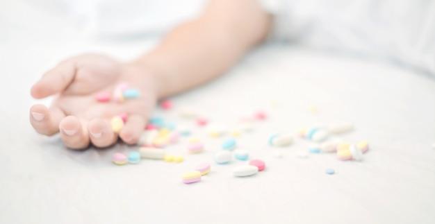 Chiuda in su della mano dell'uomo con le pillole che commettono il suicidio overdosing sul farmaco Foto Premium