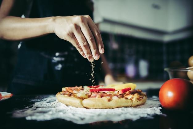 Chiuda in su della mano della donna che mette origano sopra il pomodoro e la mozzarella su una pizza. Foto Gratuite