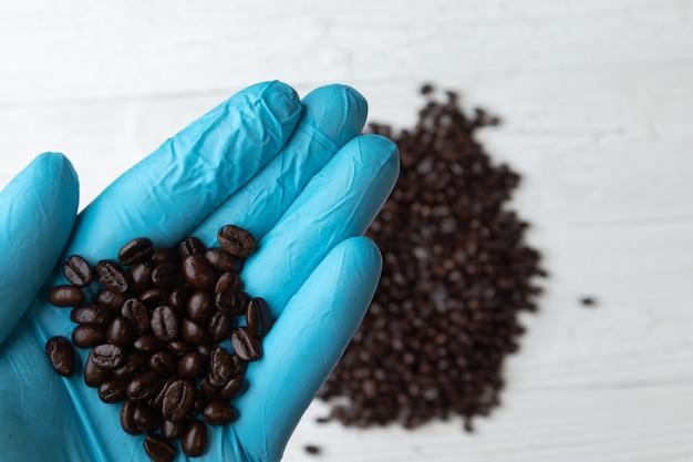 Chiuda in su della mano in guanto blu che tiene i chicchi di caffè di arrosto Foto Premium