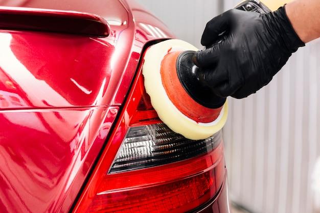 Chiuda in su della persona che pulisce l'esterno dell'automobile Foto Gratuite