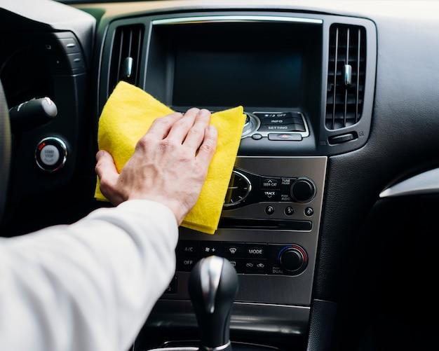 Chiuda in su della persona che pulisce l'interno dell'automobile Foto Gratuite