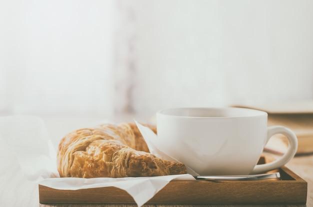 Chiuda in su della tazza di caffè con il croissant sulla tabella di legno con il tono dell'annata Foto Premium