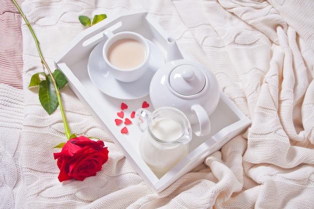 Chiuda in su della tazza di tè con la rosa rossa sul vassoio bianco Foto Premium