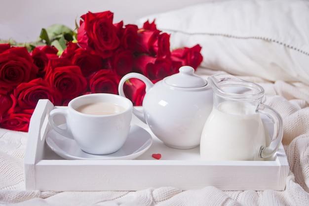 Chiuda in su della tazza di tè con le rose rosse sul vassoio bianco Foto Premium