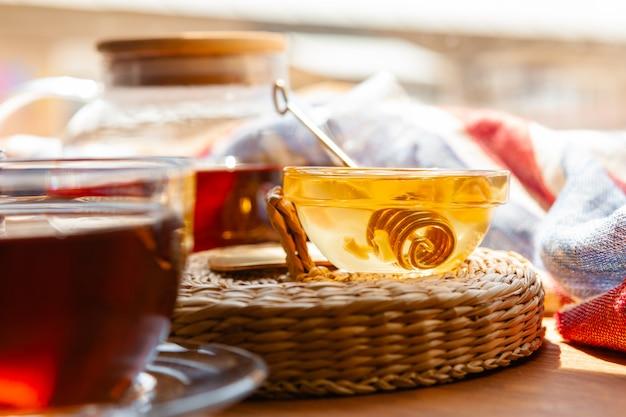 Chiuda in su della tazza di tè di vetro con miele Foto Premium