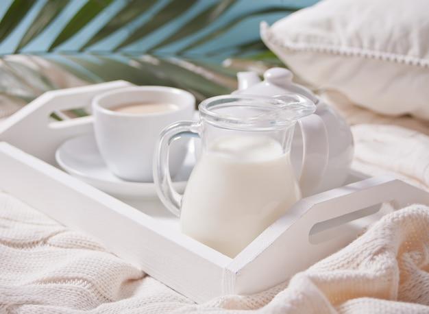 Chiuda in su della tazza di tè, latte, teiera sul vassoio bianco. Foto Premium