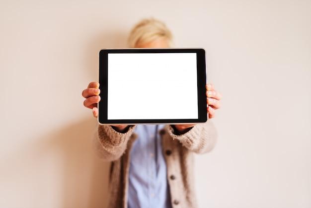 Chiuda in su della vista di messa a fuoco del tablet con schermo bianco modificabile. immagine sfocata di una donna in piedi dietro la tavoletta e tenendolo. Foto Premium