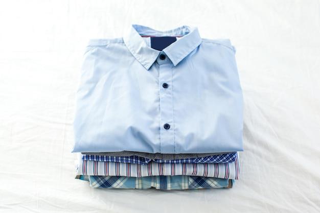 Chiuda in su delle camicie stirate e piegate sul tavolo a casa Foto Premium