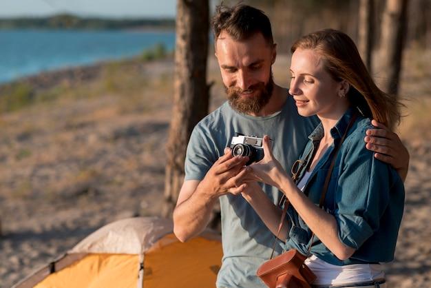 Chiuda in su delle coppie che installano una macchina fotografica Foto Gratuite