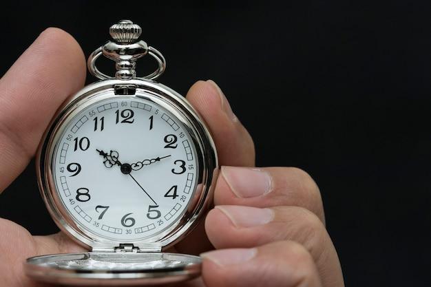 Chiuda in su delle mani con orologio da tasca retrò Foto Premium