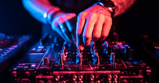 Chiuda in su delle mani del dj che controllano un tavolo da musica in un night-club. Foto Premium