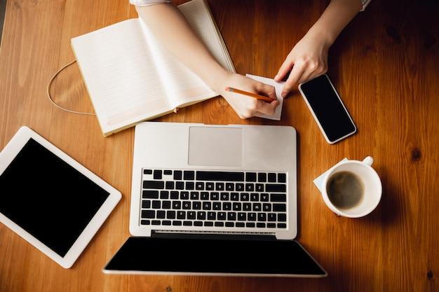 Chiuda in su delle mani femminili caucasiche durante il lavoro in ufficio, studiando, vista dall'alto Foto Gratuite