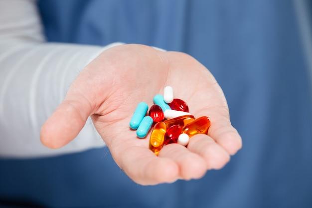 Chiuda in su delle pillole maschii della holding della mano del medico Foto Gratuite