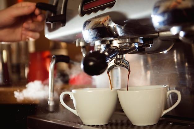 Chiuda in su di caffè espresso che versa dalla macchina del caffè in tazze bianche. Foto Premium