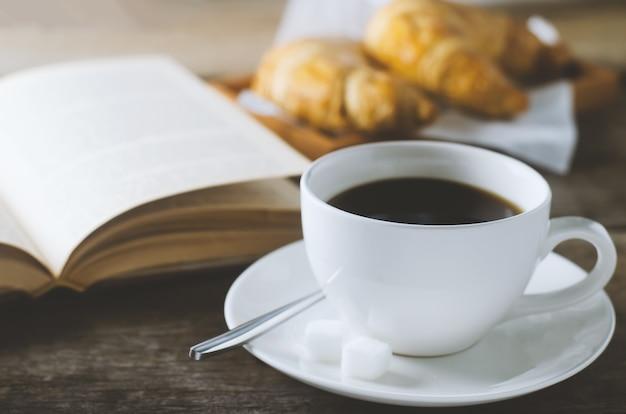 Chiuda in su di caffè nero con il libro e il croissant sulla tabella di legno Foto Premium