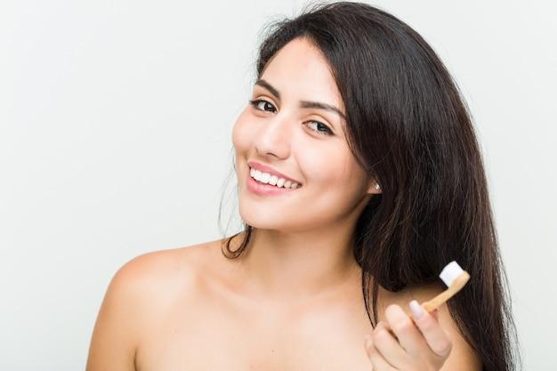 Chiuda in su di giovane bella e donna ispanica naturale che tiene uno spazzolino da denti Foto Premium