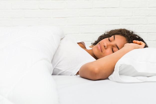 Chiuda in su di giovane donna stanca dell'afroamericano che dorme sulla base Foto Premium