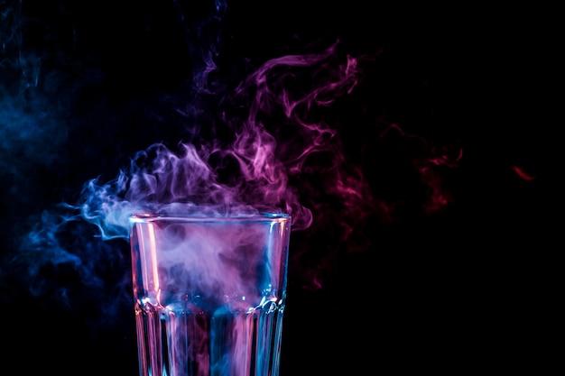 Chiuda in su di nuovo vetro con fumo rosa multi-coloured morbido da vape su una priorità bassa isolata nera Foto Premium