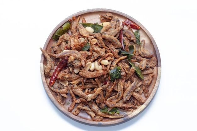 Chiuda in su di piccoli pesci fritti nel grasso bollente croccanti sul piatto Foto Premium