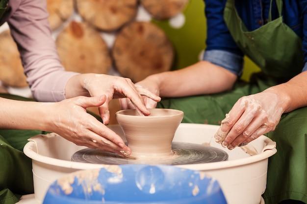 Chiuda in su di un'argilla sclulpting del vasaio della donna Foto Premium