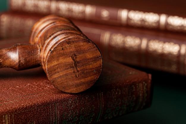 Chiuda in su di un martelletto e di un libro di legno marroni Foto Premium
