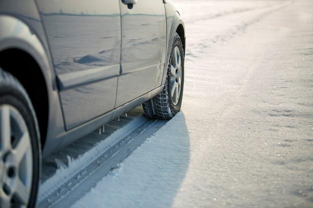 Chiuda in su di una gomma di automobile parcheggiata sulla strada nevosa il giorno di inverno. trasporto e sicurezza. Foto Premium