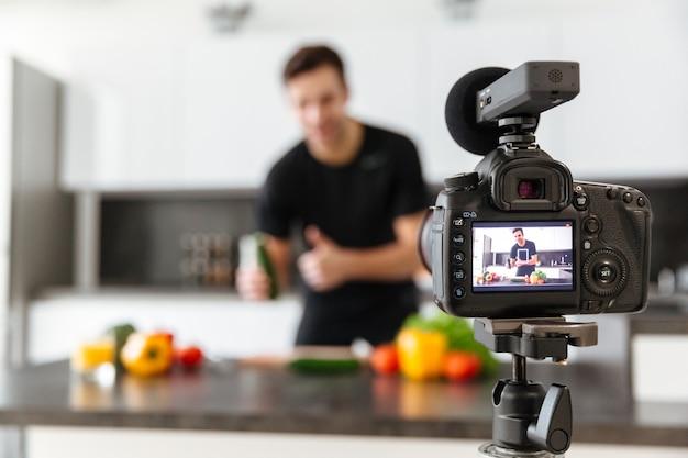Chiuda in su di una videocamera che filma il giovane blogger maschio sorridente Foto Gratuite