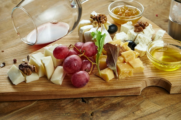 Chiuda in su sul piatto di formaggio servito con le noci, l'uva, il miele. vista dall'alto su diversi tipi di formaggio sulla superficie scura Foto Premium