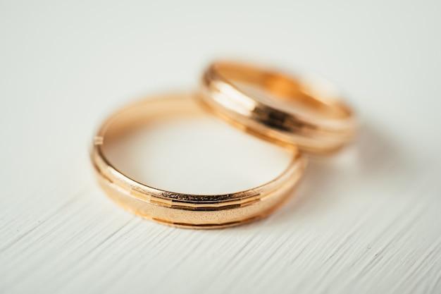 Chiuda su degli anelli di oro di nozze d'intersezione su fondo di legno bianco Foto Premium