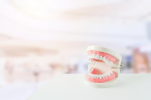 Chiuda su dei denti bianchi modellano con gomma rossa e specchio dentario sul fondo della sfuocatura Foto Premium