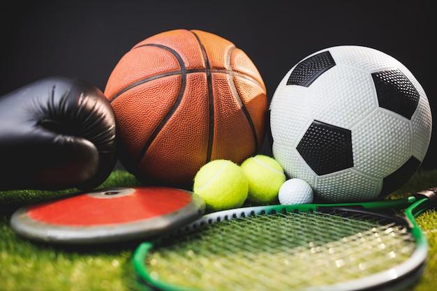 Chiuda su dei guantoni da pugile e palle da golf e discus di tennis di tennis di calcio di pallacanestro Foto Premium