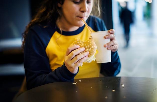 Chiuda su dell'adolescente che mangia il concetto di obesità dell'hamburger Foto Gratuite