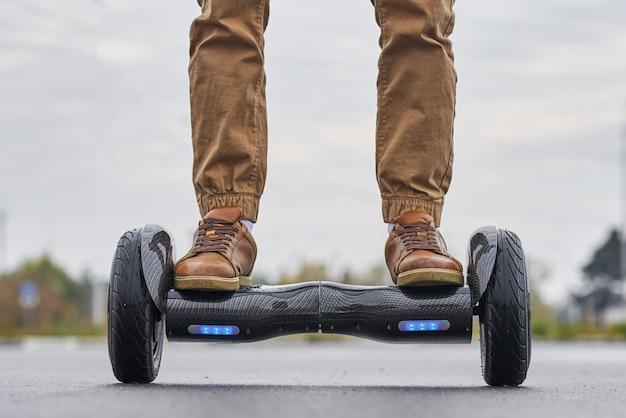 Chiuda su dell'uomo che usando la strada asfaltata di hoverboard, i piedi sul motorino elettrico all'aperto, vista frontale Foto Premium