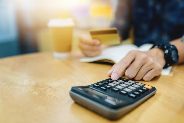 Chiuda su dell'uomo di affari che lavora con la mano di dati finanziari facendo uso del calcolatore al caffè del caffè. Foto Premium