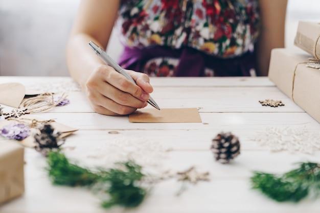 Chiuda su della donna delle mani che scrive la lista dei desideri e la cartolina di natale vuote sulla tavola di legno con la decorazione di natale. Foto Premium