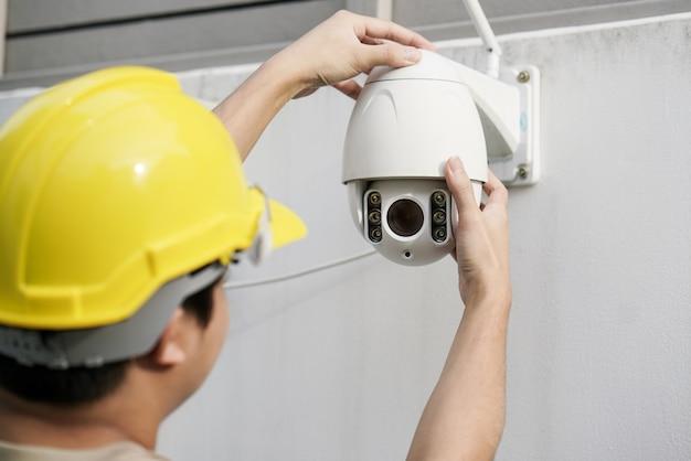 Chiuda su della macchina fotografica maschio di fixing cctv del tecnico sulla parete Foto Premium