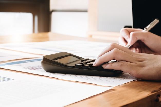 Chiuda su della penna di tenuta della mano del ragioniere o della donna di affari che lavora al calcolatore per calcolare i dati di gestione Foto Premium