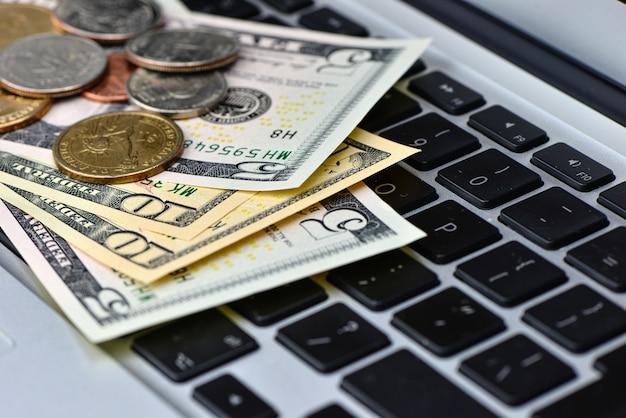 Chiuda su delle banconote e delle monete del dollaro sulla tastiera del computer portatile, concetto online di affari Foto Premium