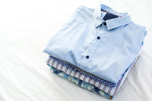 Chiuda su delle camice stirate e piegate sulla tavola a casa Foto Premium