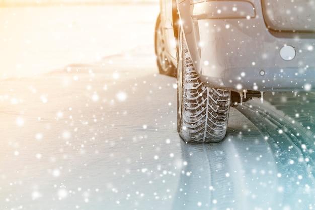 Chiuda su delle gomme di gomma delle ruote di automobile in strada profonda della neve dell'inverno Foto Premium