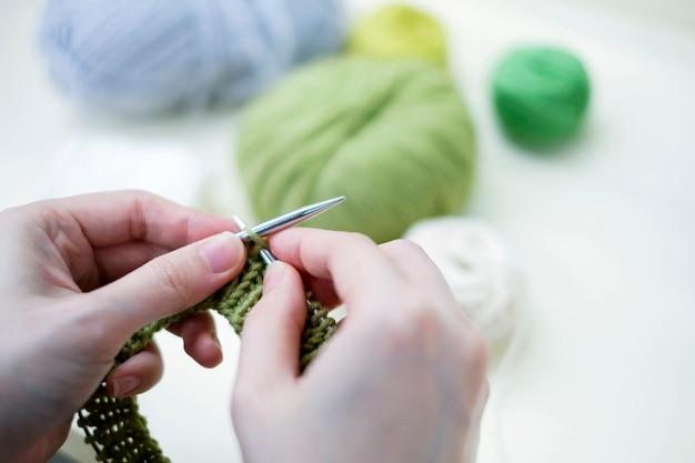 Chiuda su delle mani della donna che tricottano a casa Foto Premium