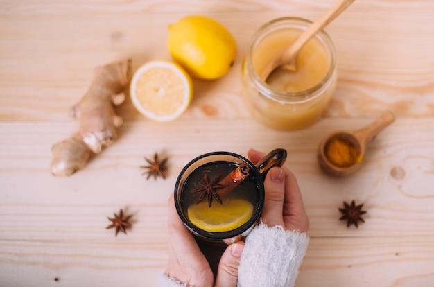 Chiuda su delle mani femminili che tengono la tazza di acqua calda con il limone Foto Premium