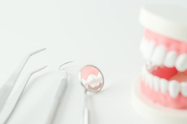 Chiuda su dello specchio dentario con i denti modellano e l'attrezzatura dentaria su fondo bianco Foto Premium