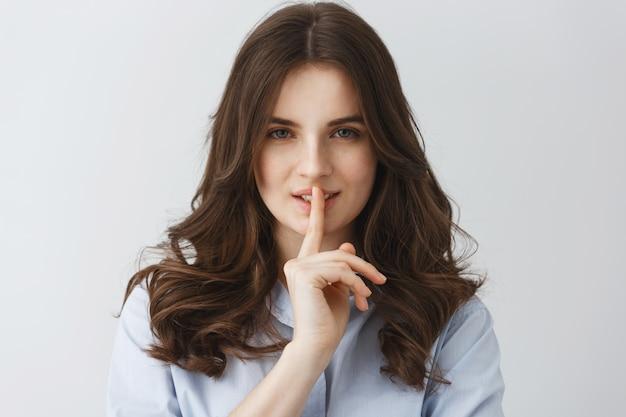Chiuda su di giovane dito sexy della tenuta della ragazza vicino alla bocca che fa il gesto di silenzio con l'espressione civettuola del fronte. Foto Gratuite