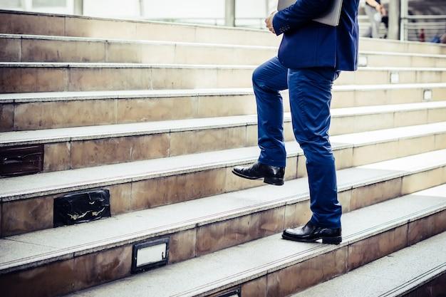 Chiuda su di giovane uomo d'affari che cammina di sopra fuori dell'ufficio. Foto Gratuite