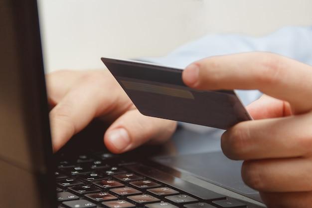 Chiuda su di un uomo che compera online facendo uso del computer portatile con la carta di credito Foto Premium