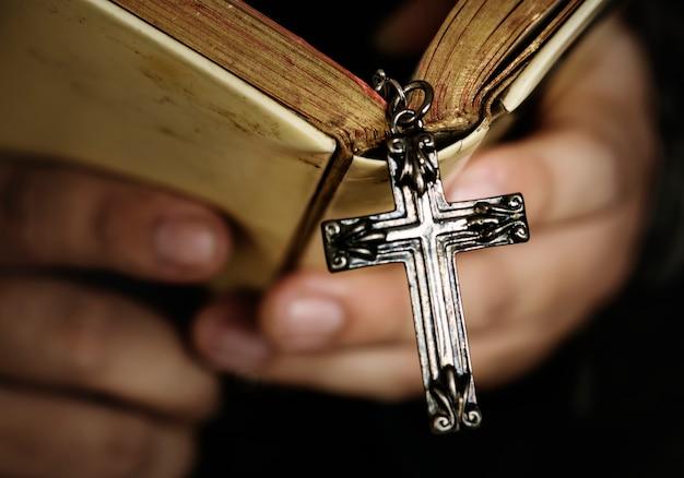Chiuda su di un uomo che legge una bibbia con la religione d'attaccatura e il concetto di credenza trasversali Foto Gratuite