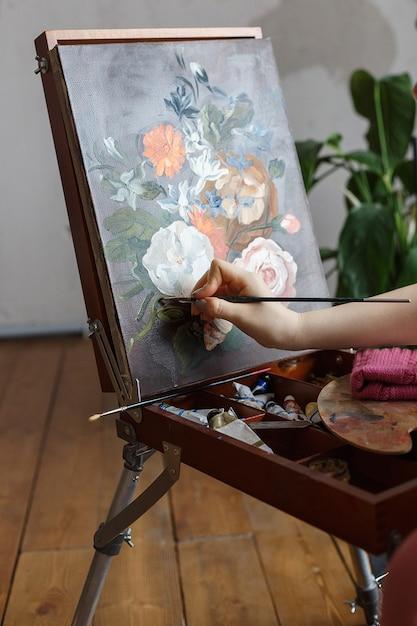 Chiuda su sulle mani dell'artista con l'immagine dei fiori della pittura della spazzola su un cavalletto Foto Premium